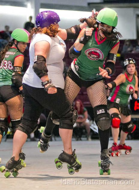 Demolition Barbie, a.k.a. Jessamyn Williams, crashes through the pack during the Treasure Valley Roller Derby All Stars bout with Sonoma County (Calif.) Saturday June 14, 2014 at CenturyLink Arena in Boise.