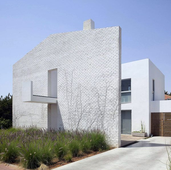 House N, in Israel: a house built behind a wall, shaped like a simple line drawing of a house, designed to shelter the actual house from the street. Ingenious approach to privacy.