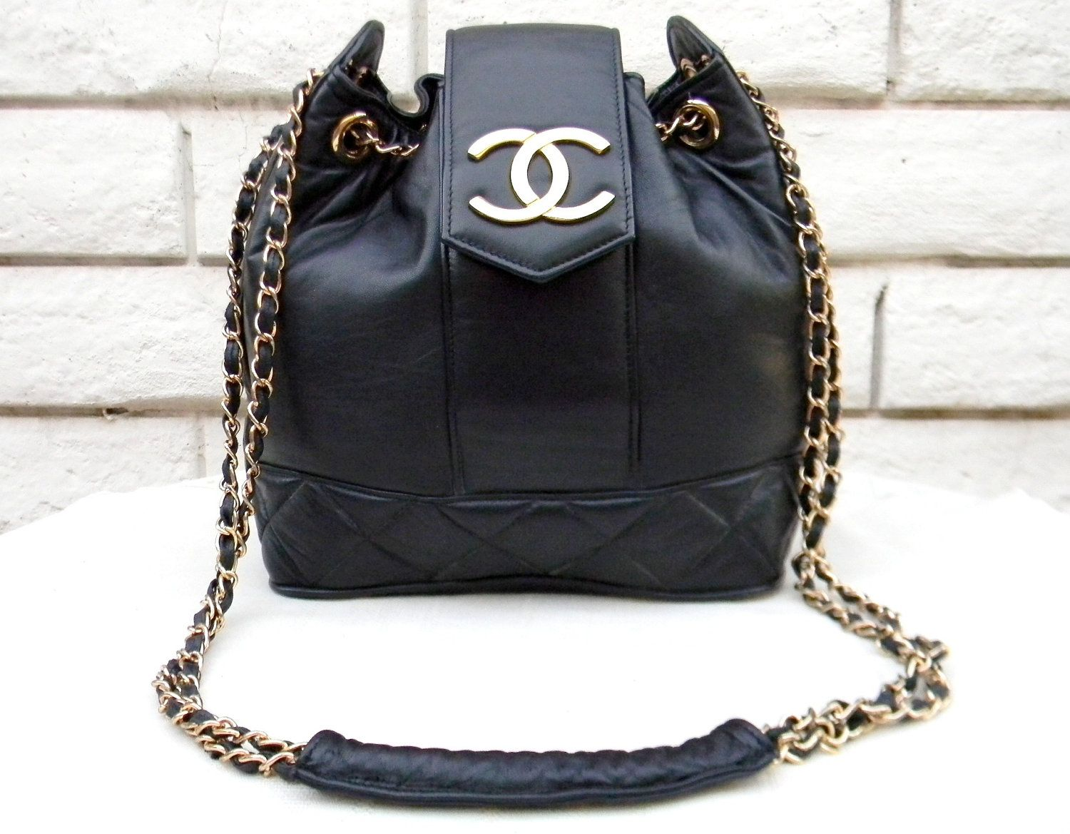bd550cab8fae Vintage Chanel leather bucket bag with chain and flap with chanel logo.  Inventory