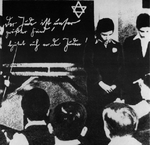 """Two young Jews are humiliated in front of their classmates at a school in Germany in 1935.  Before the Holocaust began in earnest, the Nazis began a policy of ever-increasing discrimination, intolerance and outright abuse against the Jews, from the top offices of Govt., right down to classrooms and schoolyards.  The words on the blackboard read, """"The Jew is our greatest enemy! Beware of the Jew!"""""""