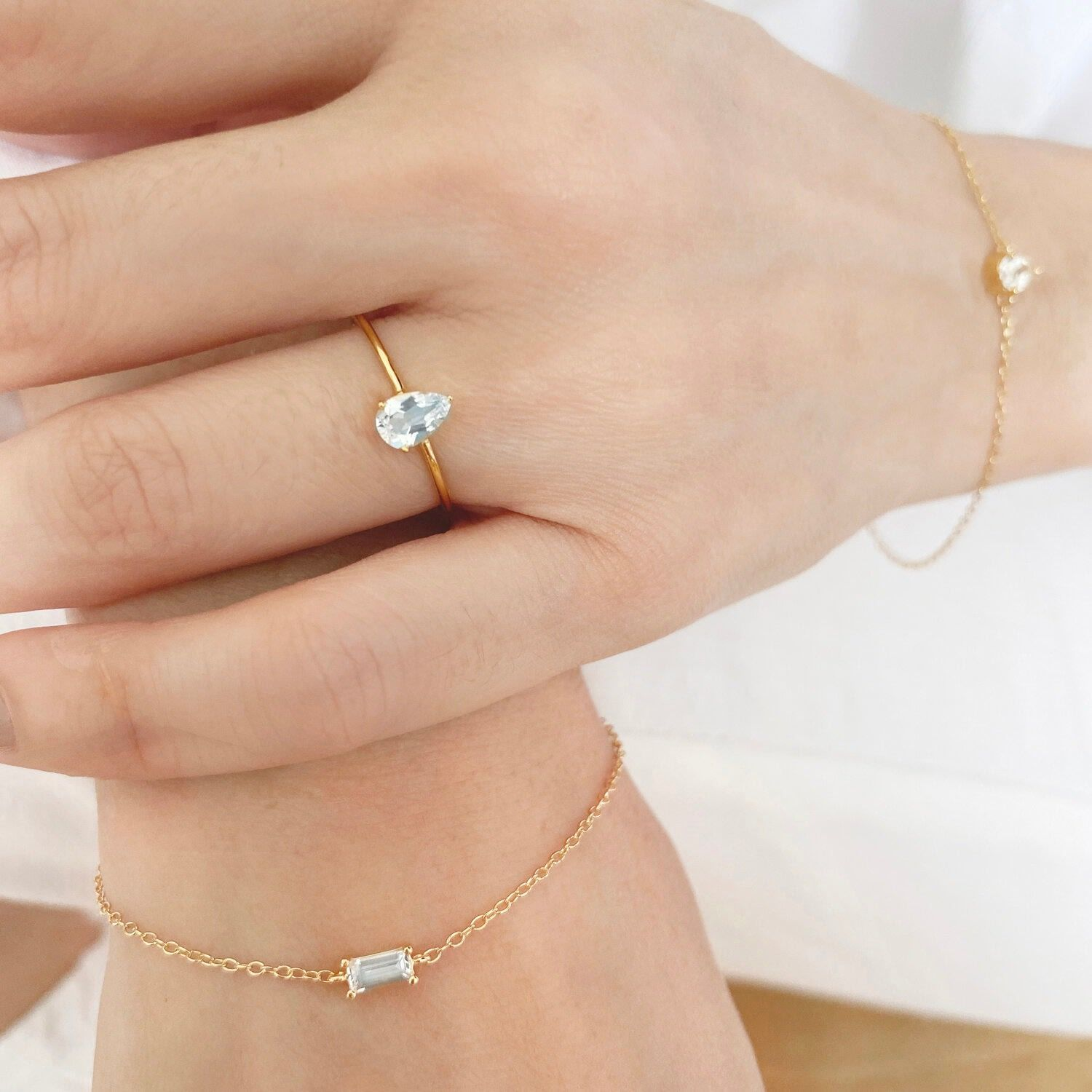 The Baguette Topaz Gold Sterling Silver Bracelet is the perfect everyday piece. This dainty demi-fine piece features a rectangle-cut White Topaz gem on a classic jewel chain - wear this bracelet as a stand-alone piece or layer with other different shapes. Consciously crafted with 925 sterling silver bases, premium gold vermeil and White Topaz stones, Essentials celebrates the four classic shapes in the jewelry world - circle, square, rectangle and pear. Each gem is cut in a similar method to dia
