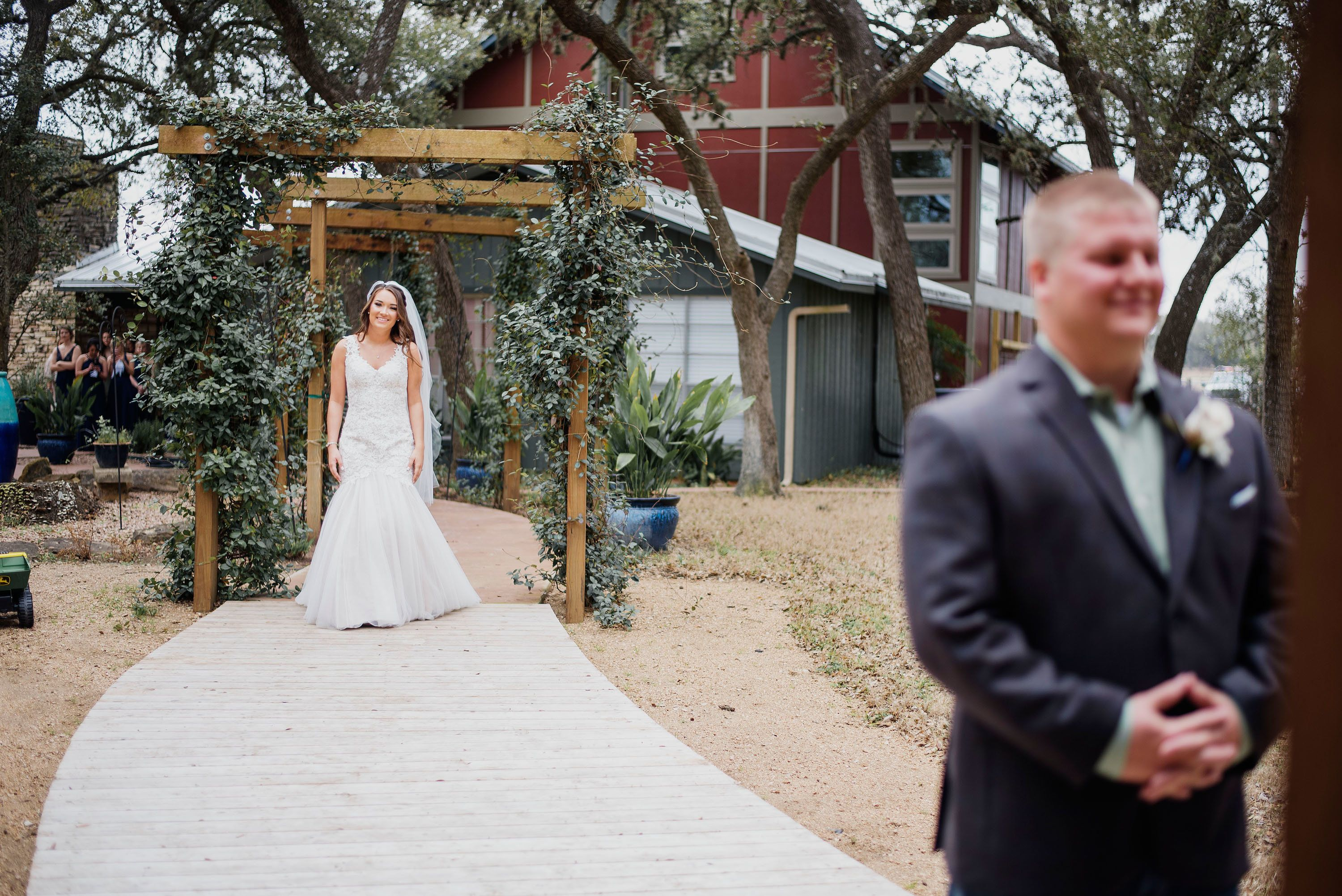 Bride walks to meet her groom while he waits for their first look