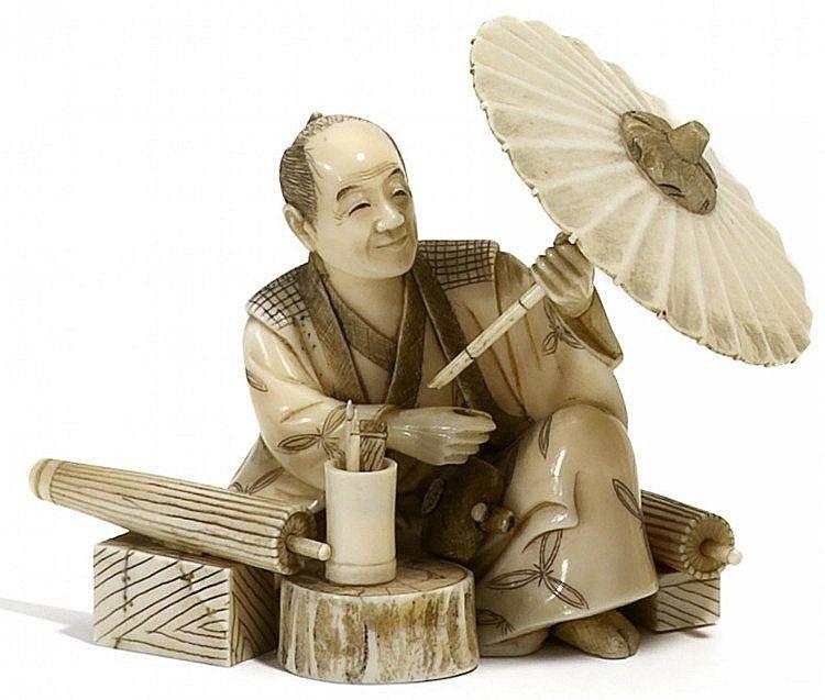 OKIMONO: SCHIRM-HERSTELLER, ELFENBEIN. Meiji-Zeit. Sehr fein geschnitzt und graviert, Details schwarz eingefärbt. H.5,7cm. Signiert auf roter Lack-Reserve: Tamayuki, vgl. LA, S.1072.