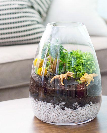 Que tal criar dinossauros em casa? Hahahah essa uma idéia mega criativa em que você só precisa de um vaso de plantas ou um aquário, plantas e pedrinhas e dinossauros ou outros bonecos