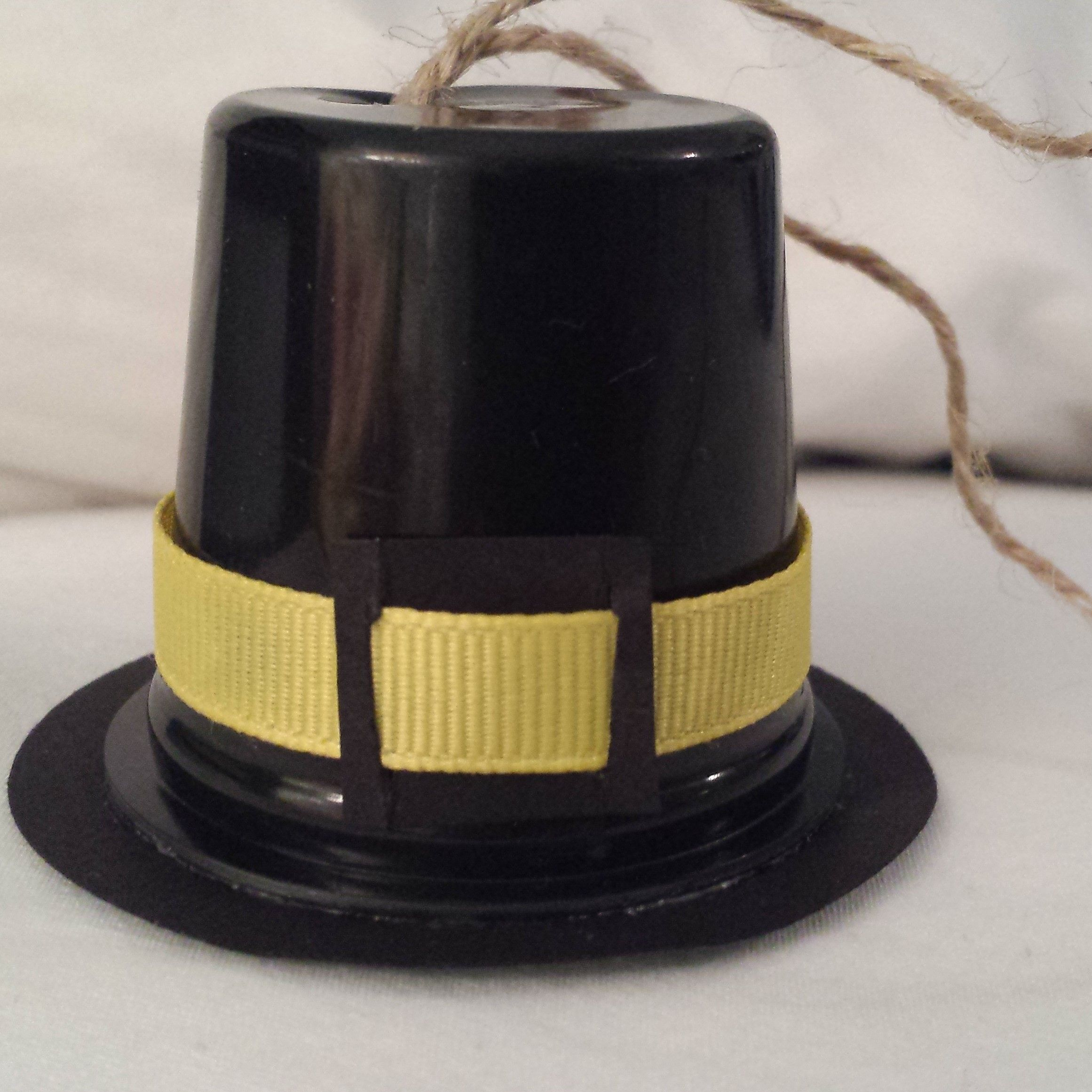 Pilgrim Hat - Black K-Cup; 2 inch circle punch; black cardstock; Yellow Grosgrain ribbon; Cardstock buckle; Twine looped and knotted in bottom hole
