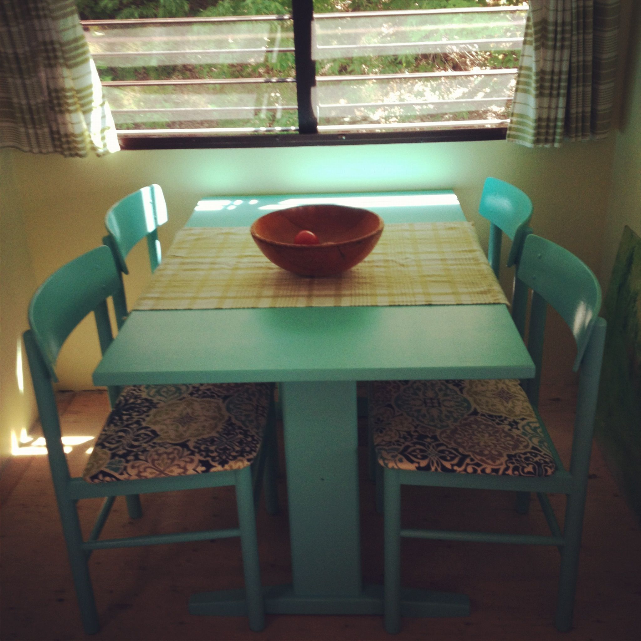 We repainted our wooden table & chairs and recovered the seats. Curtains made of tea towels!