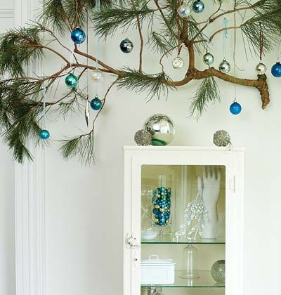 A pine branch mounted on the wall with ornaments hanging from it.