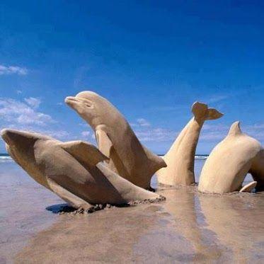 Delfines esculpidos en arena