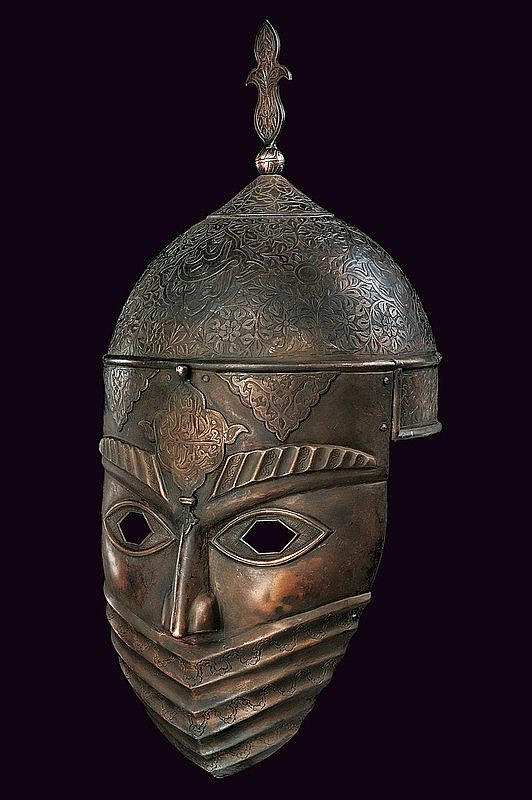 Helmet with hemispherical, iron skull, decorated with engraved cartouches featuring inscriptions in Arabic surrounded by woven racemes, at the top a lily-shaped cusp with round knot and conical base; at the mask, fixed with rivets, relieved decorations and engravings depict a human face with a band covering the lower portion of the face, at the centre of the forehead another cartouche with inscription, eyes with hexagonal holes. Coppery covering. provenance: Iran
