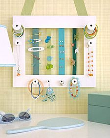 Jewelry frame for little girls. This one is made from a picture frame with spools and ribbons attached and can be hung from a picture hook. Spools hold necklaces, rings, and elastic bands; the ribbons hold barrettes, clips, and earrings.