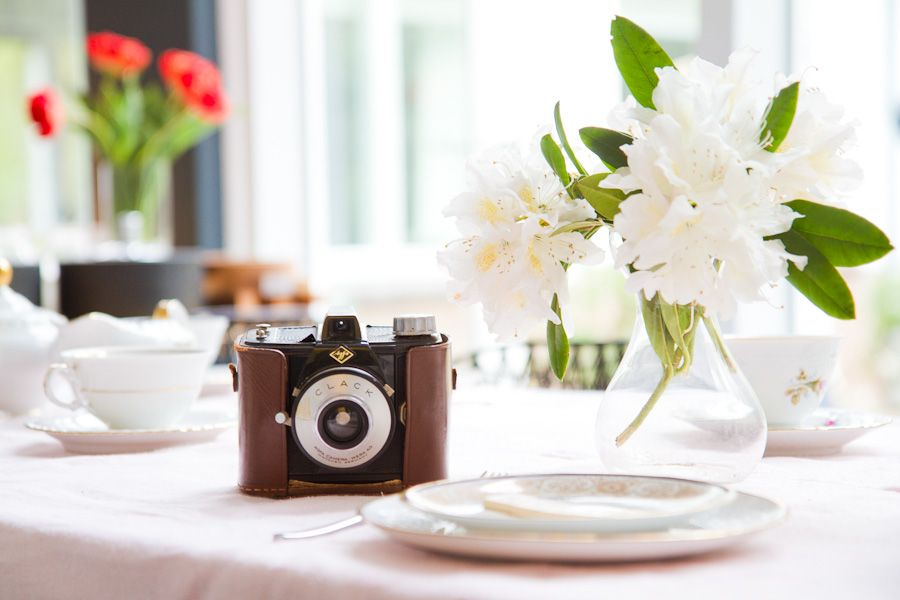 Vintage camera, flowers and table setting