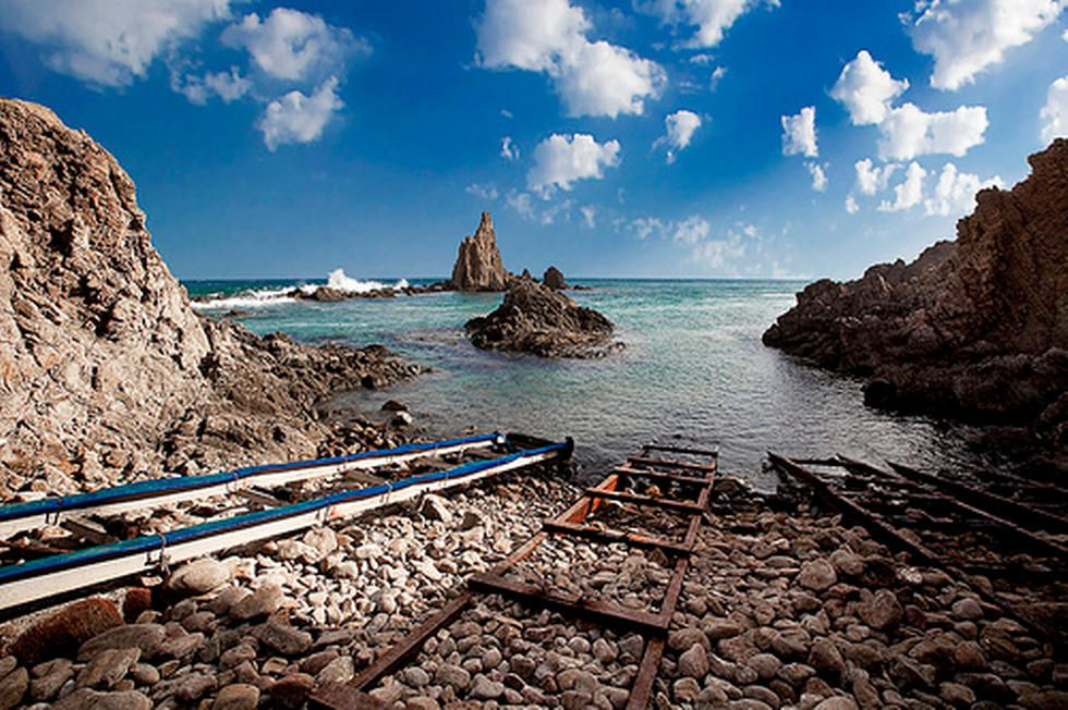 El Parque Natural de Cabo de Gata está lleno de rincones mágicos, pero si me tuviera que quedar con uno sería con el Arrecife de Las Sirenas. Se trata de unas chimeneas volcánicas de caprichosas formas. ¿ Lo mejor? poderlas observar desde la pequeña cala que a penas tiene capacidad para 4 ó 5 personas y donde unas oxidadas guías para embarcaciones parecen guiarte el camino hacia los mágicos fondos marinos del Mediterráneo.