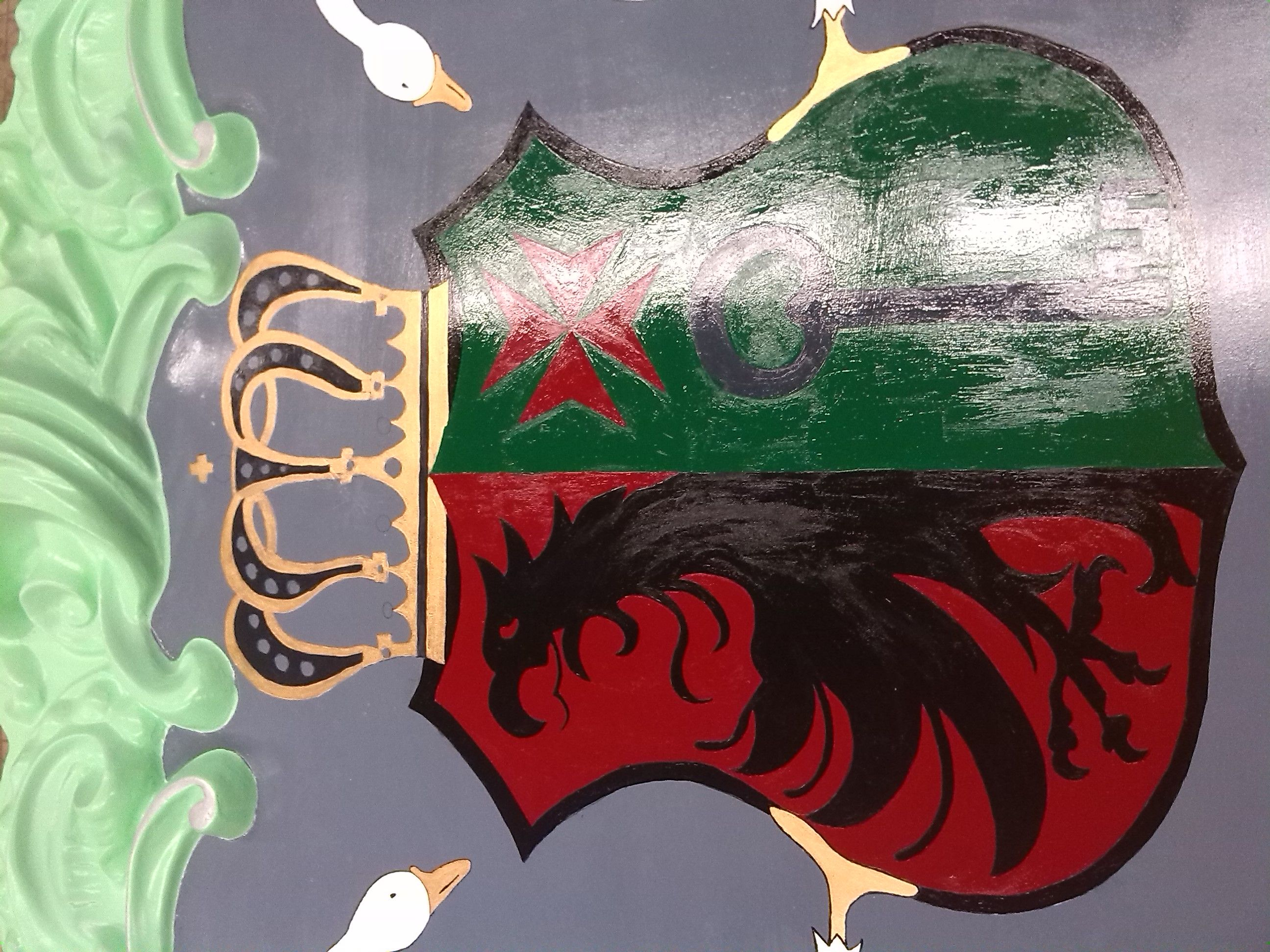 A couple days later, we painted the whole shield. The background became red with green. The color red is an evil color so it suits the griffin because it´s also evil.
