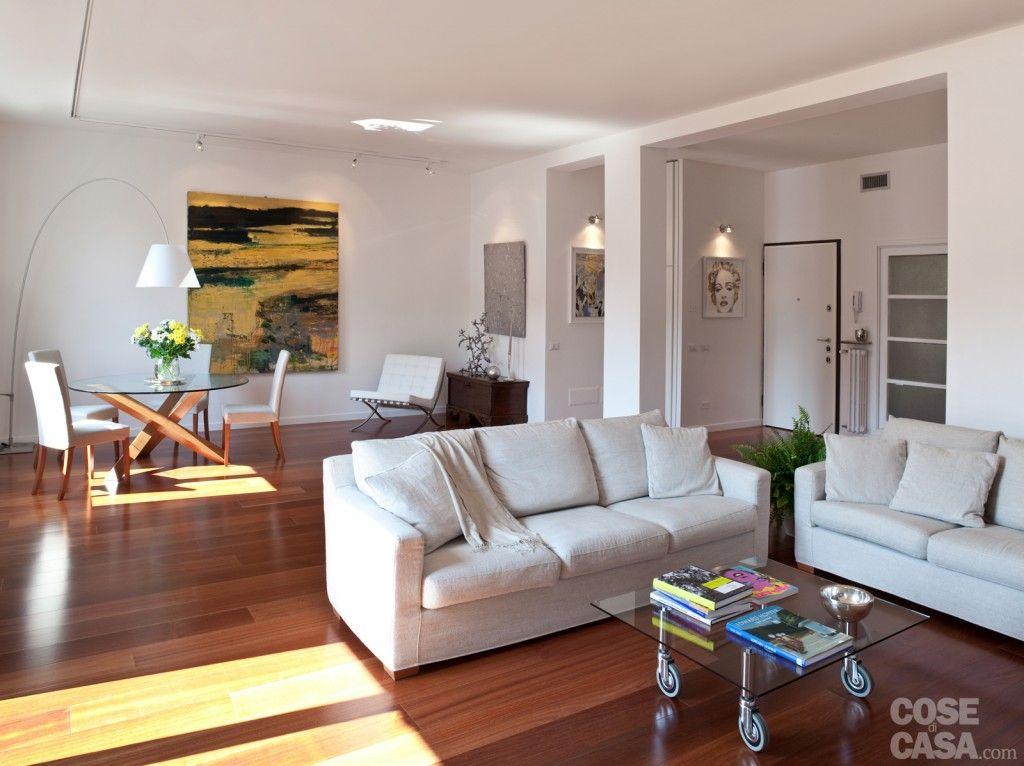 I due divani in tessuto bianco della zona conversazione sono disposti ad angolo con al centro un - Divano con mobile incorporato ...