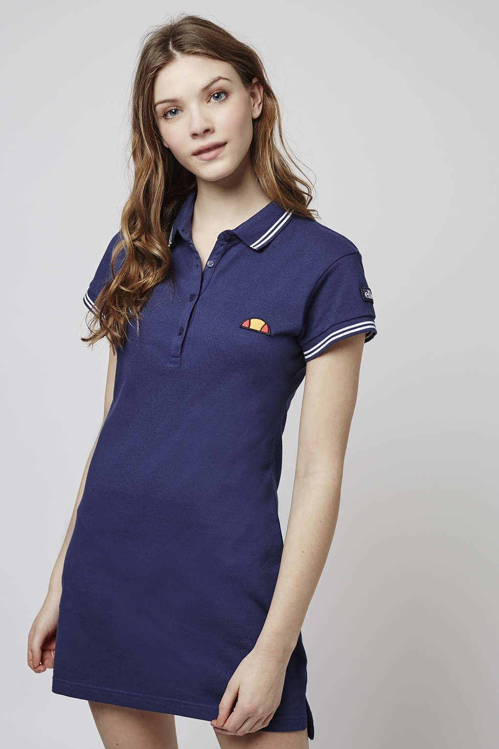a8391e977bb Give  90s nonchalance a spin in this polo t-shirt dress by Ellesse. Preppy  collar detailing and logo on the chest feature on this cotton dress.
