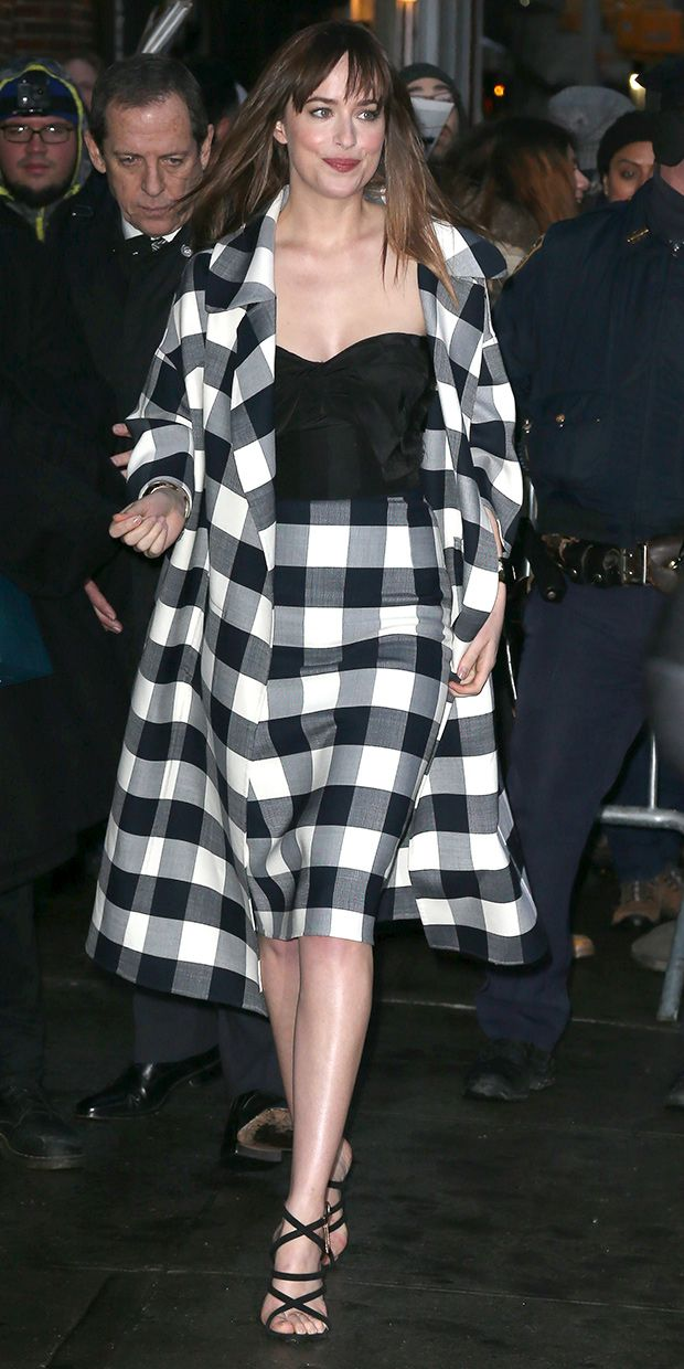 Dakota Johnson in a checkered pencil skirt and matching coat, black bustier, and strappy black heels