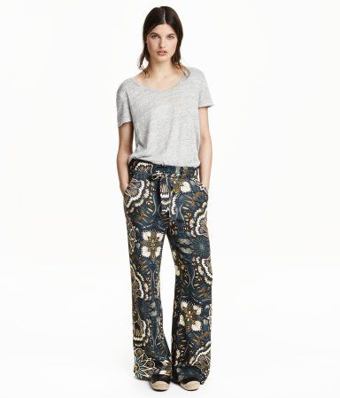 Weite Hose aus gekreppter Viskose mit Musterdruck. Die Hose hat einen elastischen Bund mit Bindegürtel und schmalen Volants oben. Seitentaschen.