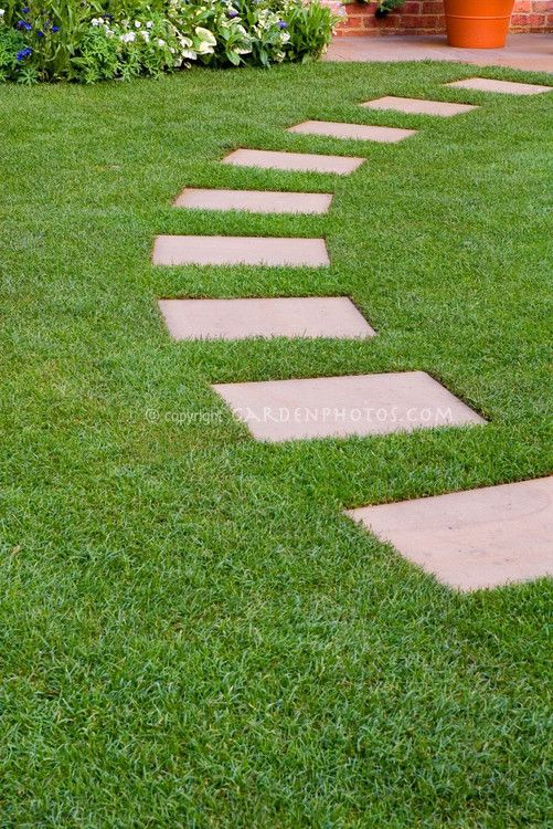 Stepping Stones In Perfect Lawn Grass Leading In An Arc To Backyard Patio With Perennial P Garden Stepping Stones Stepping Stone Paths Stepping Stone Pathway