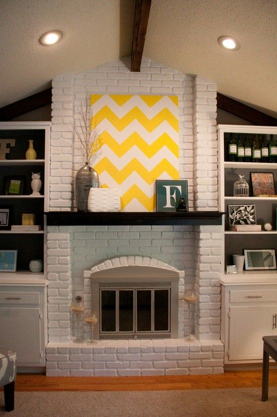White Brick Fireplace With Dark Mantel And Wood Beam
