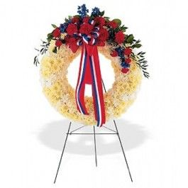 This wreath with its red, white and blue flowers displays its patriotic spirit to all. One solid white wreath arrives on an easel decorated with red carnations and blue delphinium, along with a patriotic red, white and blue ribbon.
