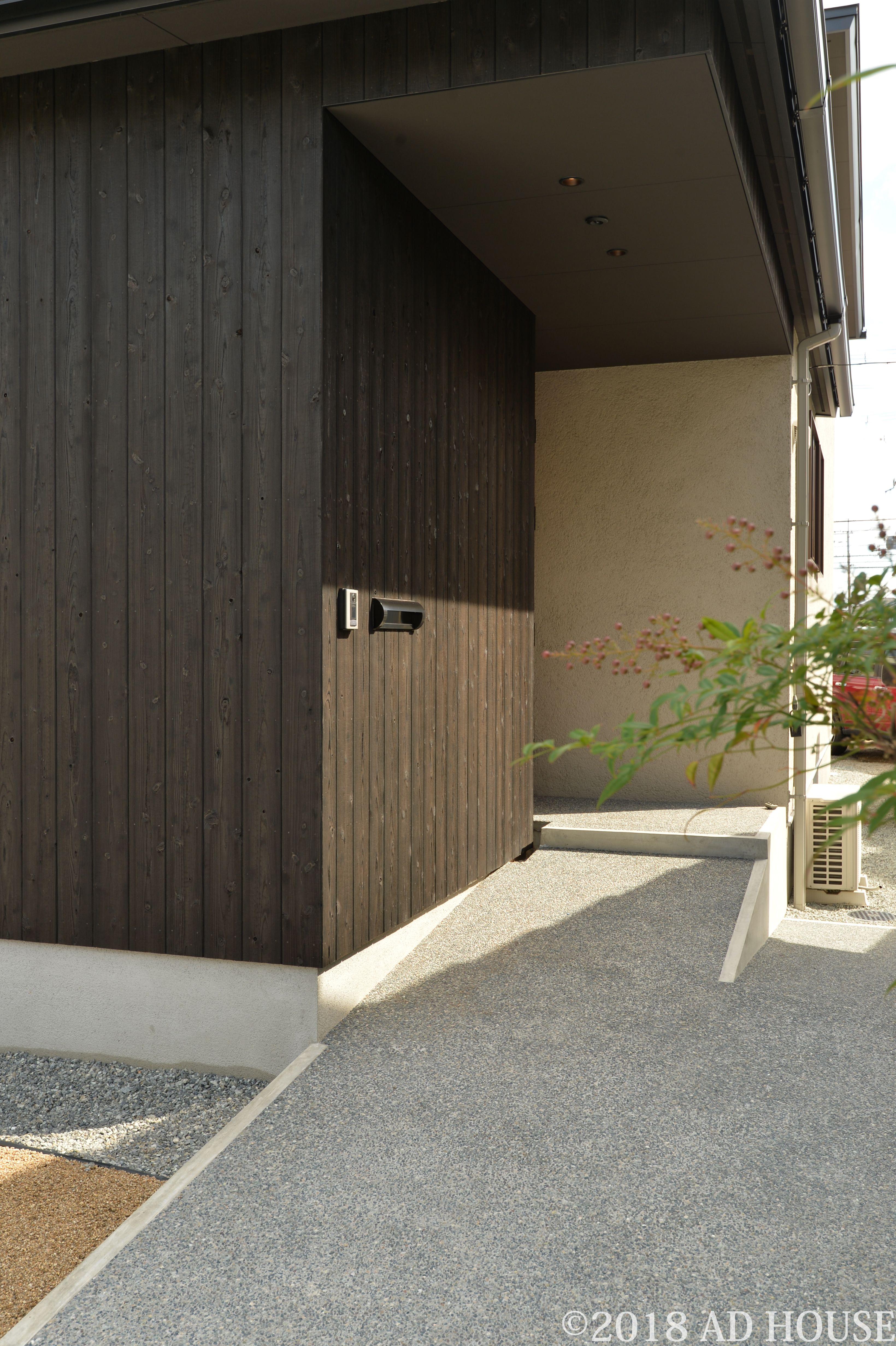 外壁は黒塗装の焼杉板 洗い出し仕上げのスロープのアプローチ 中で
