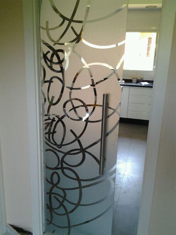 Puerta corredera de cristal templado decorado con sistema Galaxi de Krona en armazón Krona. Jambas y tapajuntas lacados en blanco.