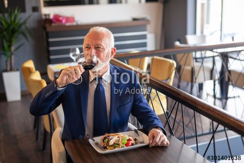 Senior businessman drinking wine in restaurant