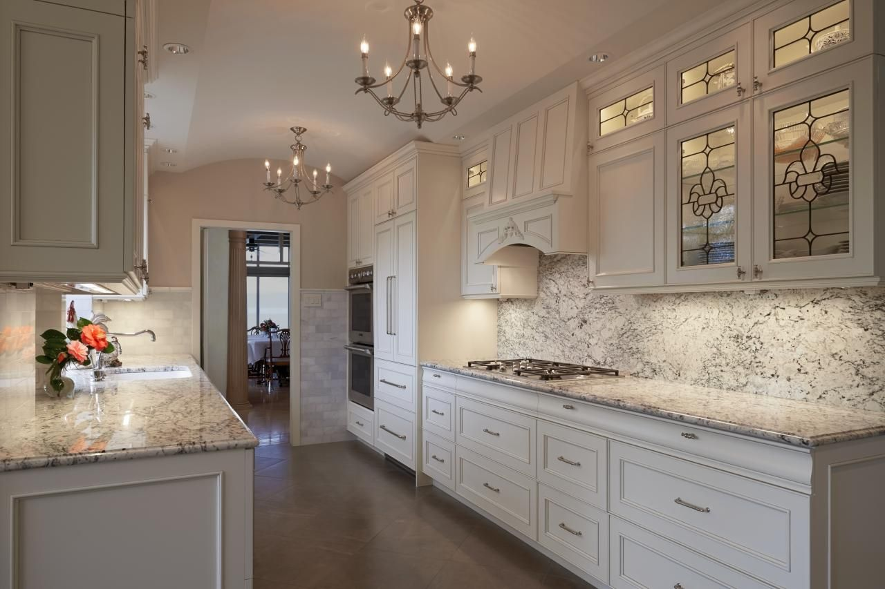 Elegant Kitchen With White Cabinets And White Ice Granite
