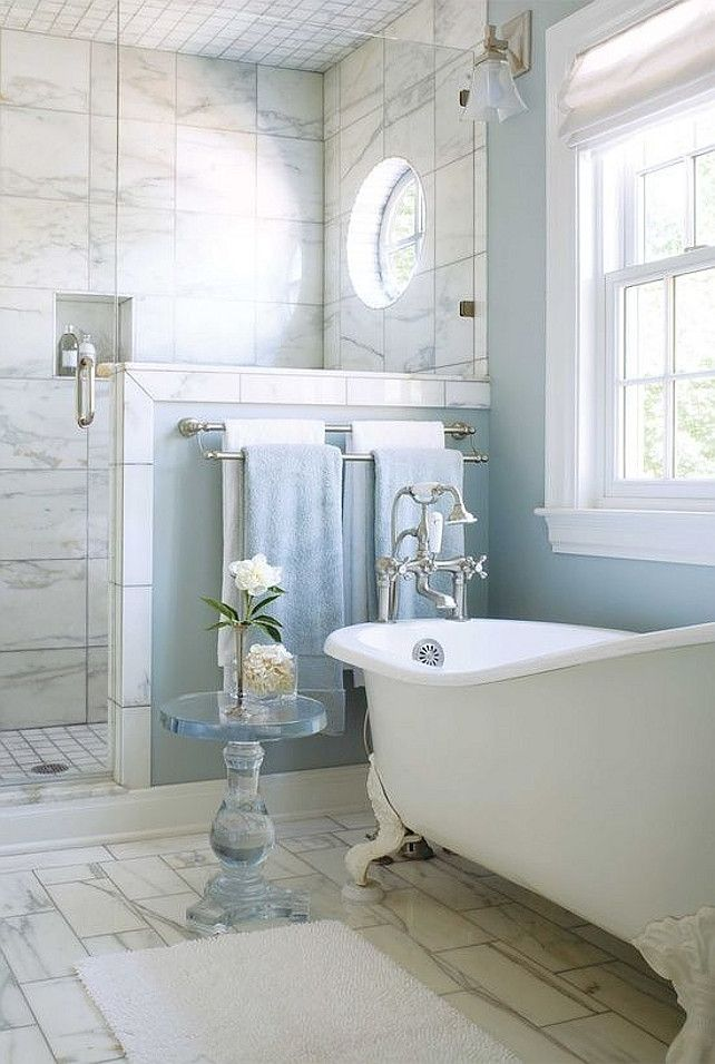 marble shower, baby blue walls and a clawfoot tub make for a very