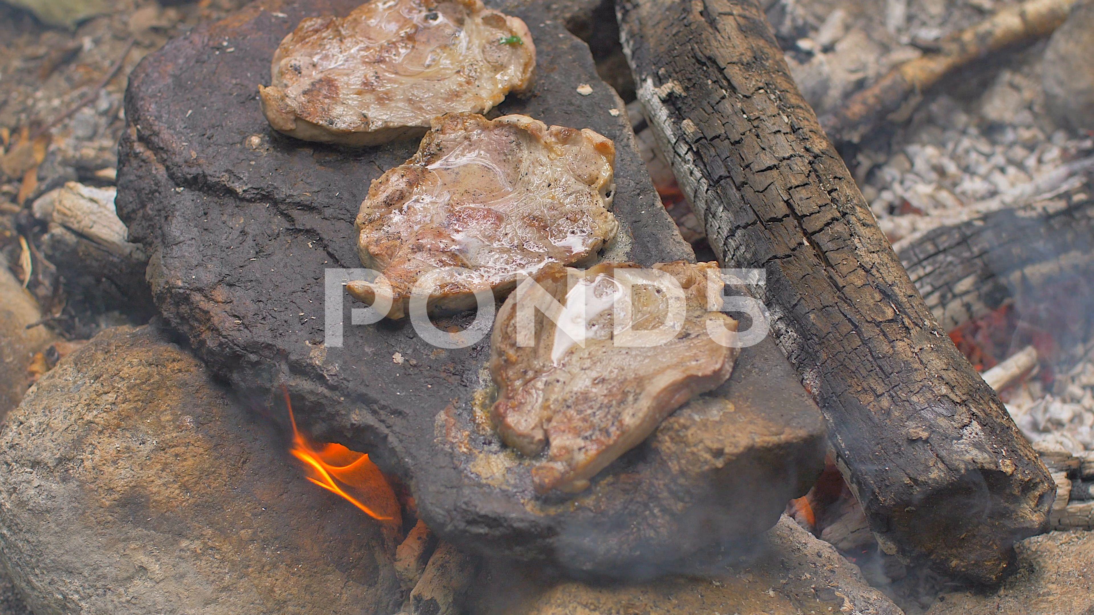 Roasting meat on a stone of fire Stock Footage stonemeatRoastingFootage