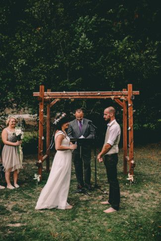 barefoot bride and groom with officiant and wood alter in background ...