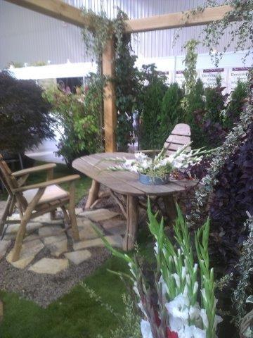 Stół i krzesła z surowego drewna pod drewnianą pergolą
