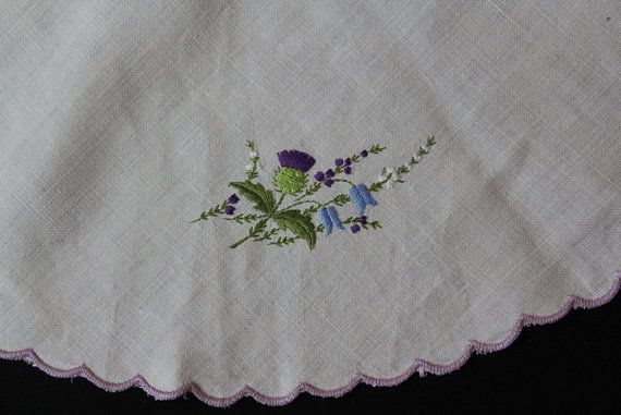 Vintage embroidered linen table centre, with lilac scalloped edging and a thistle/floral design.