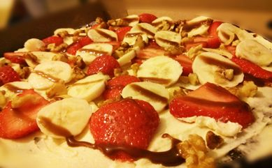 Strawberry & Banana Fruit Pizza. A dark chocolate brownie base with vanilla butter cream topped with strawberries, banana and walnuts. Finished with a coconut dusting and drizzle of chocolate sauce. Delicious.
