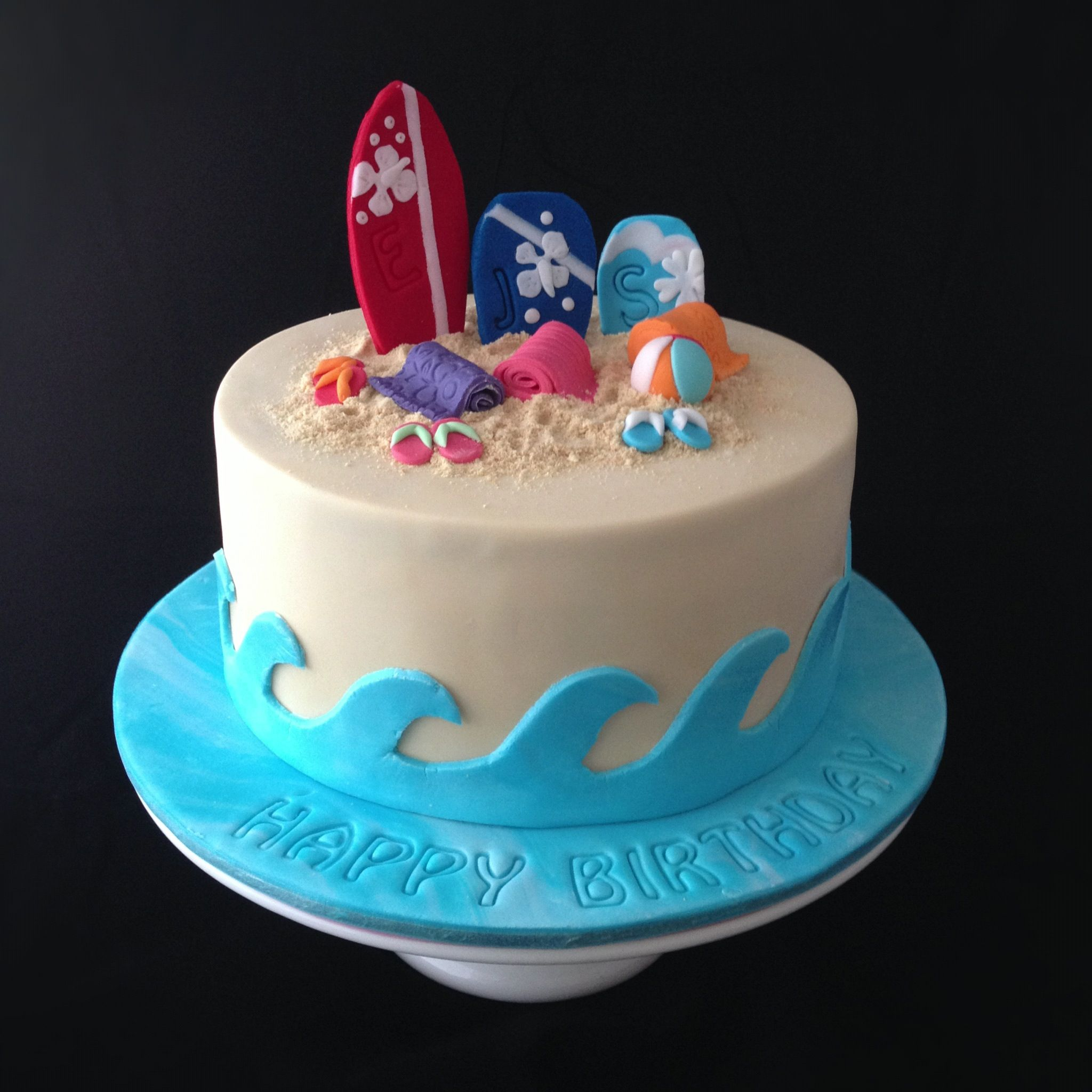 Birthday Cakes - A beach themed cake for three beach babe sisters that all celebrate their birthdays in January! Complete with edible sand, surf board, boogie boards, beach towels, beach ball and thongs!