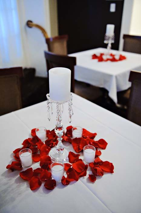 Cocktail table centerpieces white candles red rose