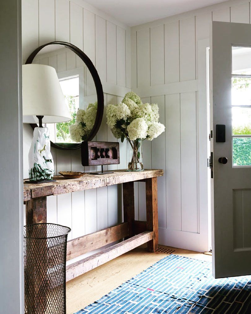 Gorgeous Entryway With A Round Mirror Above A Console Table