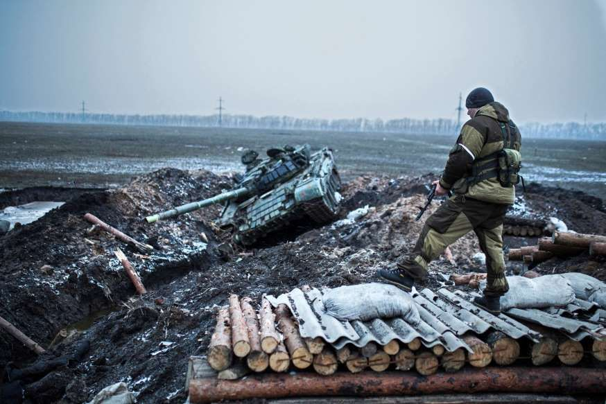 A pro-Russian rebel guards a captured former Ukrainian Army checkpoint outside Vuhlehirsk, Donetsk region, eastern Ukraine, Thursday, Feb. 5, 2015. The rebels have closed in around the town in a strategy they triumphantly refer to as the Debaltseve cauldron. Separatists recently burst through government lines in the rural settlement of Vuhlehirsk.