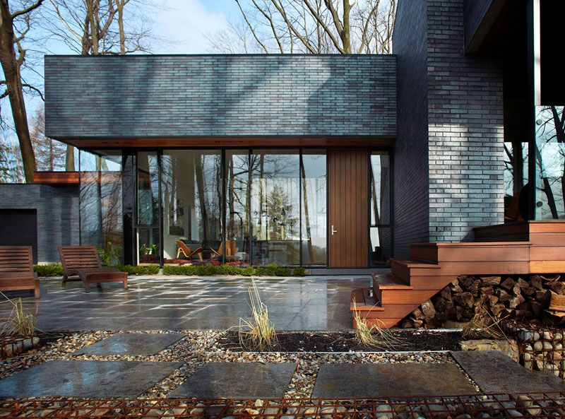 Fallsview residence: a dark brick home in the forest of canada