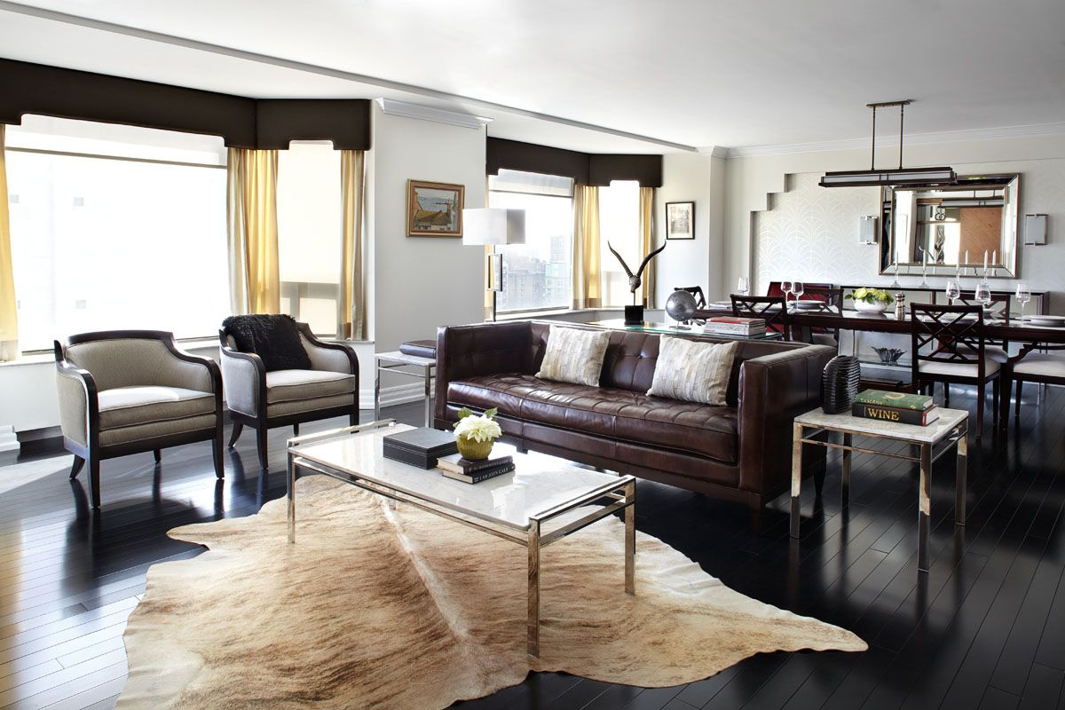 masculine living room with cowhide rug, dark brown leather sofa