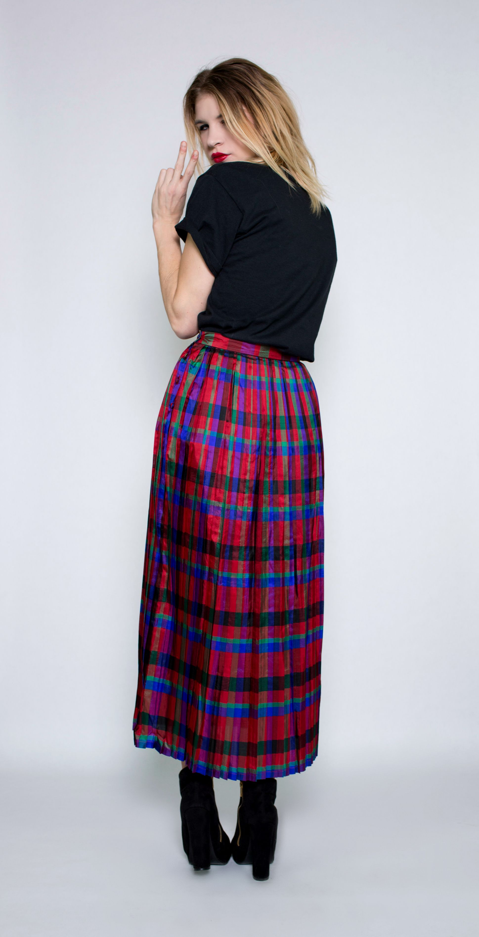 This jewel toned, high-waisted vintage plaid midi skirt is alluring and delivers the ultimate power trip. Pleated layers of lightweight fabric fall to the ankle and illuminate their colors as you move. Rock it with an old ripped tee to complete an effortlessly cool look that's sure to please.  #hipster #pleated #highwaisted #vintageskirt #holidayoutfit #holidayparty #streetstyle #model #runway #messyhair #plaidskirt #peacesign #grungefashion #hipsterfashion