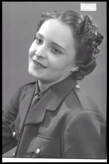 Image of a woman modelling a hairstyle and uniform for the ladies' hairdresser T. Vasco Ltd.   Maker:Bassano Studio   Production Date:1939