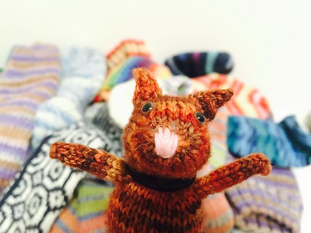 """Ever since I started to knit socks, I really wanted to make an animal from multicolored fingering weight yarn. After years of designing animals with the most common weights of DK and Worsted, I finally sat down and thought back about making that """"sock weight"""" animal. I love cats, and socks and cats is the seamless combination."""