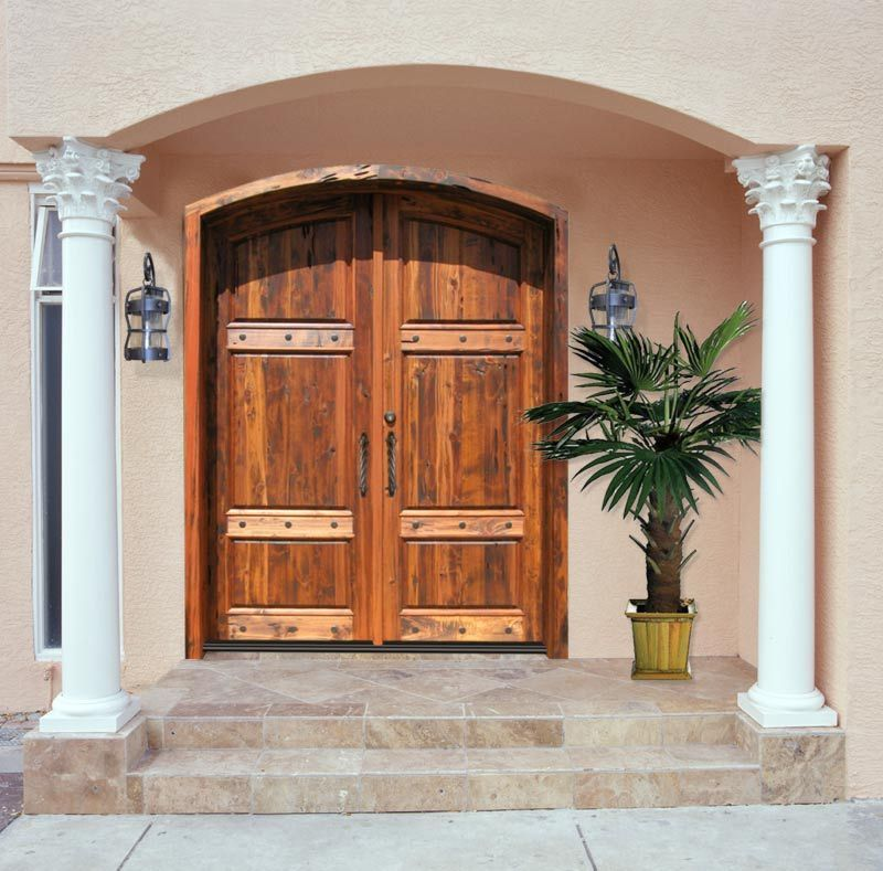 Arched Double Front Doors the columns and palm tree thing are hideous, but i love the big