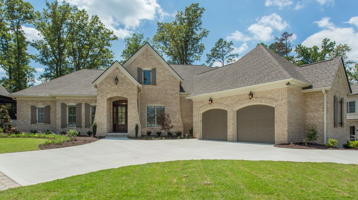 Stunning Custom Brick Home Built In Greenville Sc Love The Arched Garage Doors And Southern Style Shutters That Match Custom Homes House Exterior Light Brick