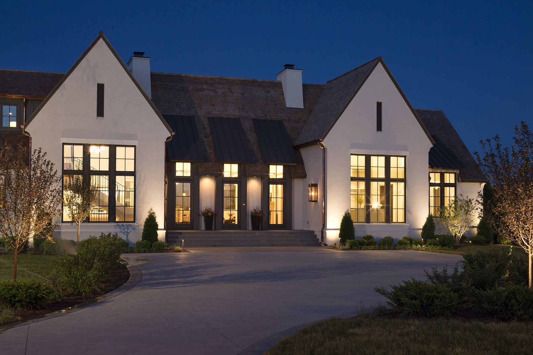 Modern Tudor Style Home With Black Windows And Exterior Accents