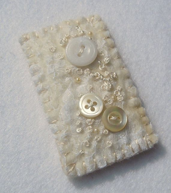 A hand embroidered, hand felted brooch in cream and white.    The base is an off white/cream coloured soft Merino wool hand felted.