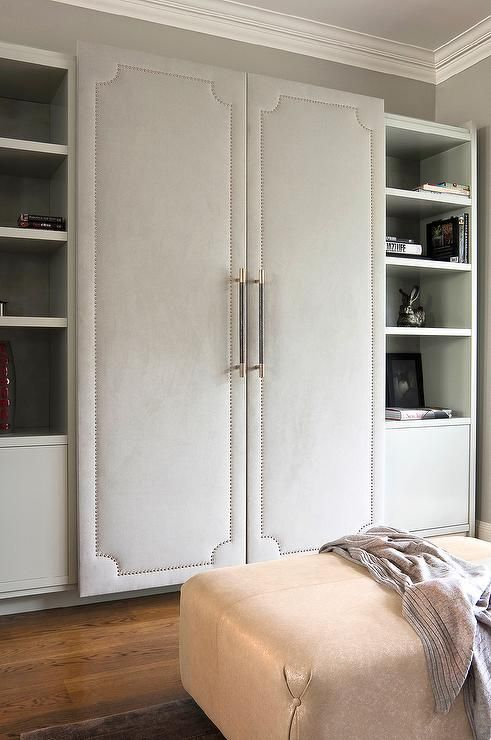 Walk In Closet Features A Wall Lined With Cabinet Fitted With Gray Fabric  Paneled Doors