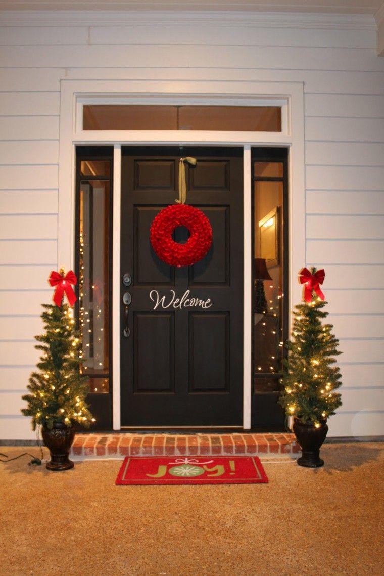 abetos pequeños con luces para decorar la puerta de entrada en navidad