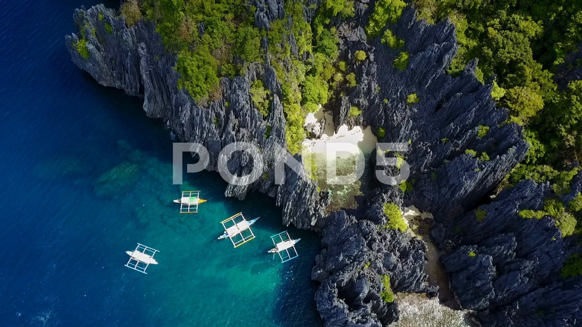 Aerial of Blue Ocean and Hidden Beach Among Jagged Rocks in Palawan Philippines Stock Footage HiddenBeachOceanAerial